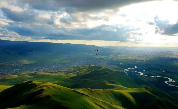 Tandem paragliding over the green mountains surrounding Ulaanbaatar Mongolia